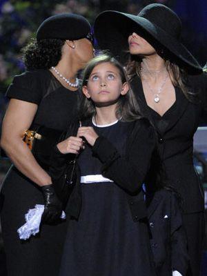 目を真っ赤にしているマイケルさんの娘パリスちゃん(11歳)。左はジャネット・ジャクソン、右はラトーヤ・ジャクソン