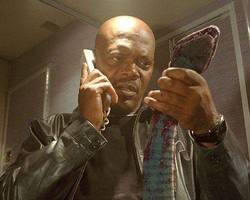 飛行機の中で、右手に受話器、左手に毒蛇……という通常ありえないショット~映画『スネーク・フライト』より