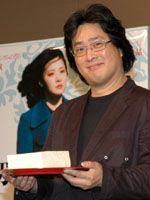 映画のキーアイテムである豆腐を持ってほほ笑むパク・チャヌク監督