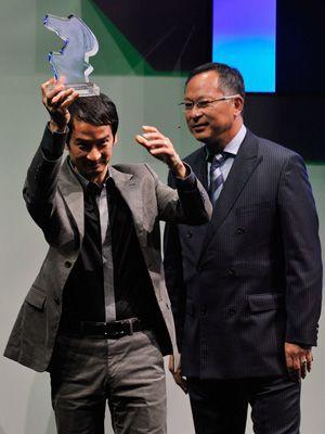 トロフィーを受け取るトラン・アン・ユン監督-(C) 2010 Getty Images