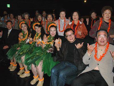 いわき市での特別上映に訪れた広野町の方々を後ろに、右から鈴木正範さん、小林正樹監督、フラガールたちと下山田支配人
