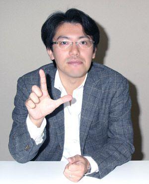 Lサインでポーズを決める佐藤P。実は本編にジェット機内の乗客役で出演しているのでチェックしてみよう!