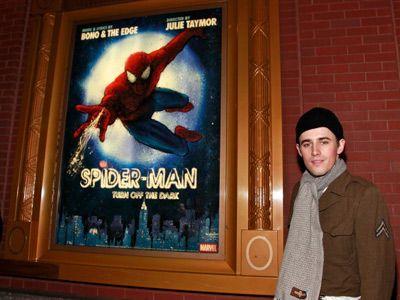 「スパイダーマン:ターン・オフ・ザ・ダーク」のポスターと写るスパイダーマン役のリーヴ・カーニー