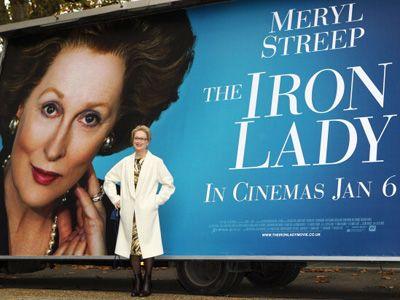 『マーガレット・サッチャー 鉄の女の涙』の巨大ポスター前でポーズするメリル・ストリープ